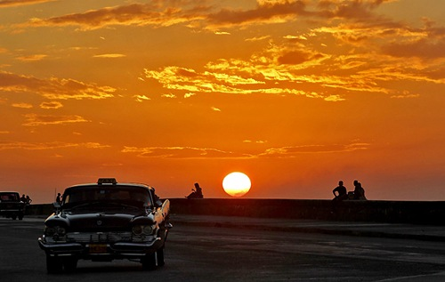 People watch the sun set along El Malecon, Havana's seafront boulevard, November 16, 2010.